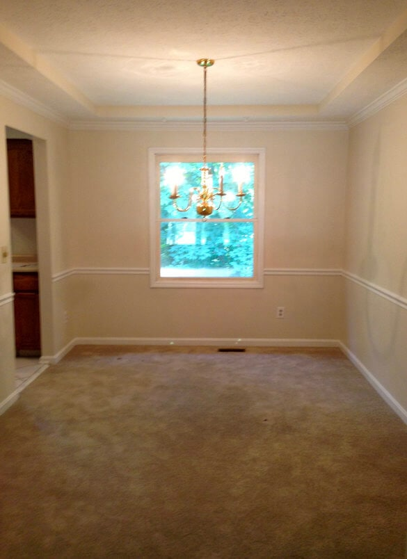 empty beige dining room with brown carpet