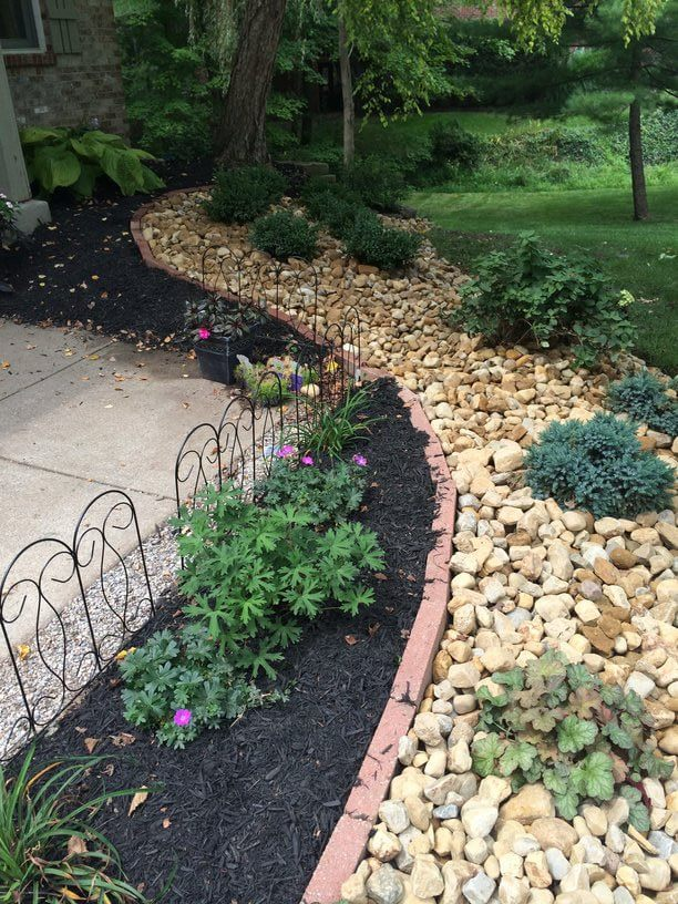river rock landscaping with flowers and boxwoods