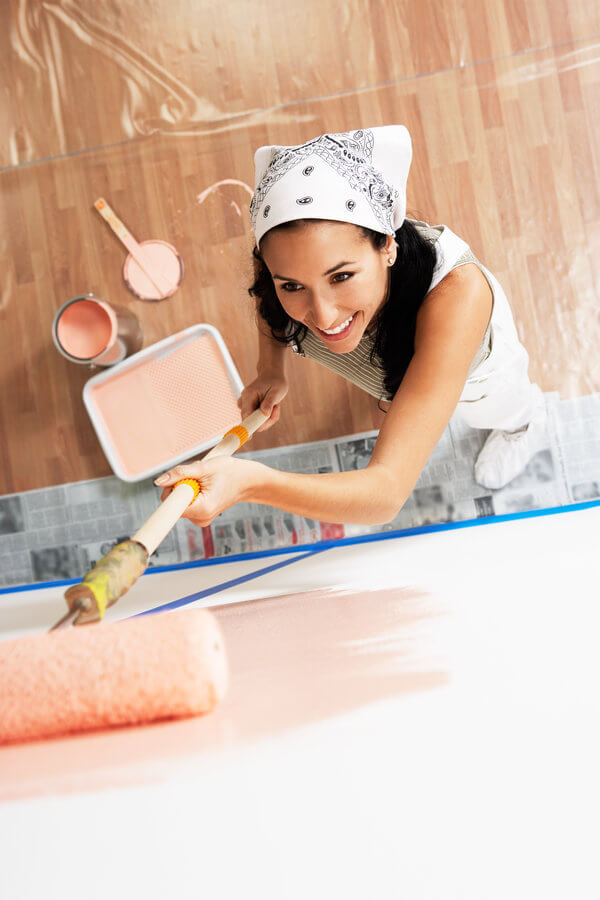 DIY woman painting a room with a roller