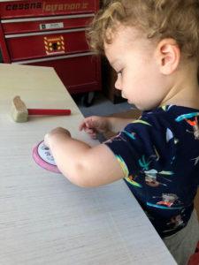 child sanding on piece of wood