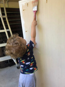 child stretching to paint toy box