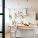 simplified minimalist white kitchen with brick backsplash