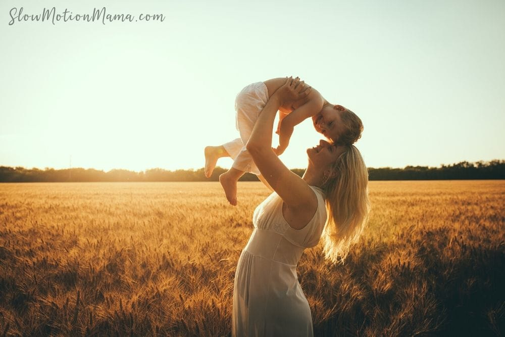 Mom with baby in a simple wheat field at sunset
