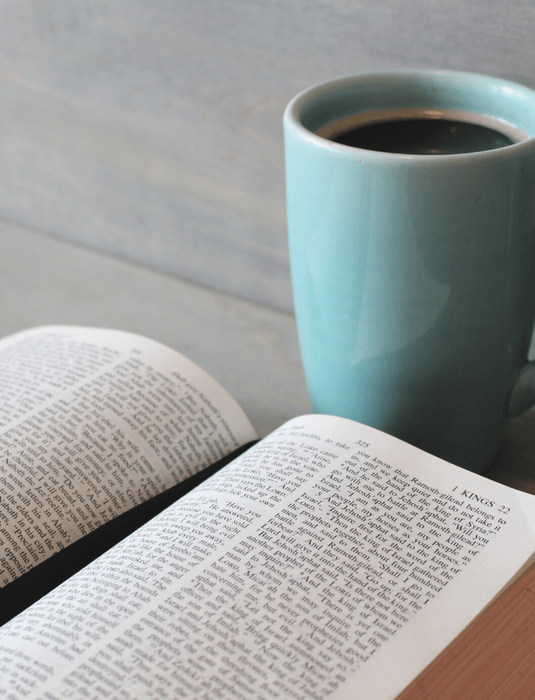 teal mug with coffee and an open bible